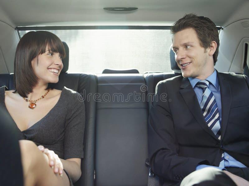 Επιχειρηματίες που μιλούν στη πίσω θέση του αυτοκινήτου στοκ εικόνα με δικαίωμα ελεύθερης χρήσης