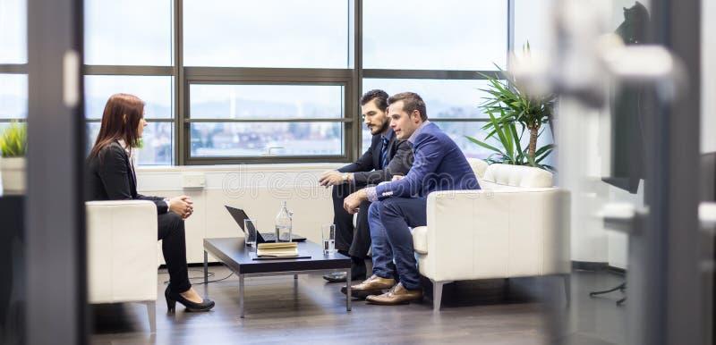 Επιχειρηματίες που παίρνουν συνέντευξη από το θηλυκό υποψήφιο για την εργασία στο σύγχρονο εταιρικό γραφείο στοκ εικόνες με δικαίωμα ελεύθερης χρήσης