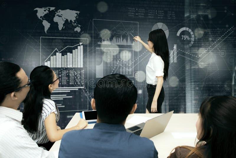 Επιχειρηματίες που παρουσιάζουν τα στοιχεία όσον αφορά τη φουτουριστική οθόνη στη συνεδρίαση στοκ εικόνα