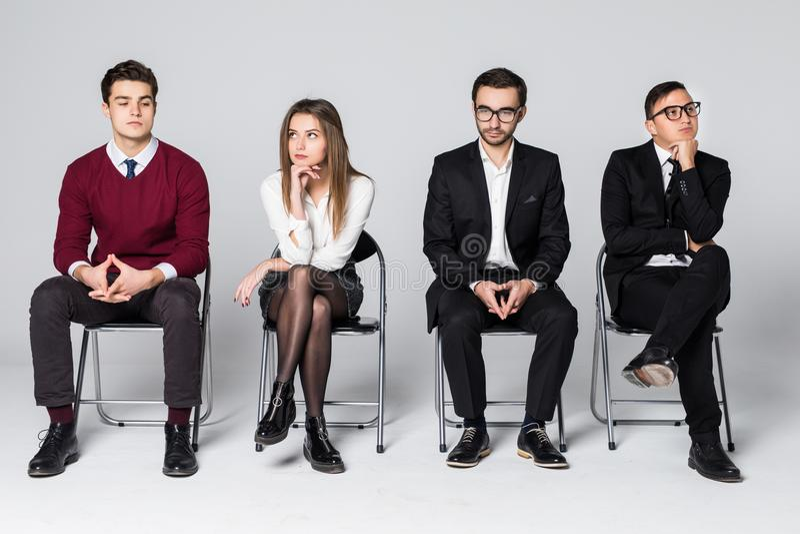 Επιχειρηματίες που περιμένουν τη συνεδρίαση συνέντευξης εργασίας στην καρέκλα που απομονώνεται στο λευκό στοκ φωτογραφία