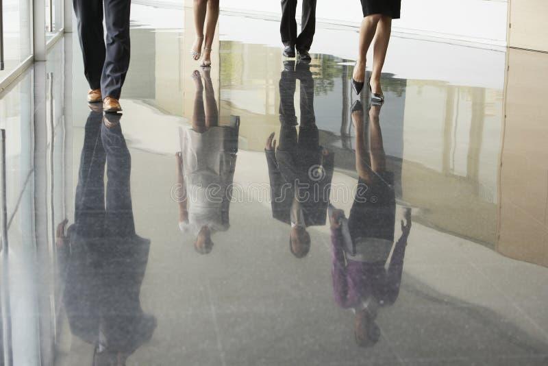 Επιχειρηματίες που περπατούν στο μαρμάρινο δάπεδο στοκ εικόνα