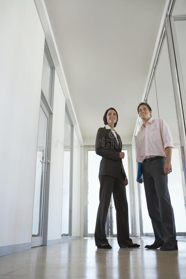 Επιχειρηματίες που στέκονται στο διάδρομο γραφείων στοκ εικόνες
