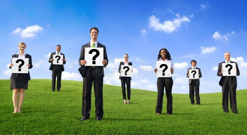 Επιχειρηματίες που στέκονται στο πάρκο και που κρατούν το σημάδι σημαδιών ερωτήσεων στοκ φωτογραφίες