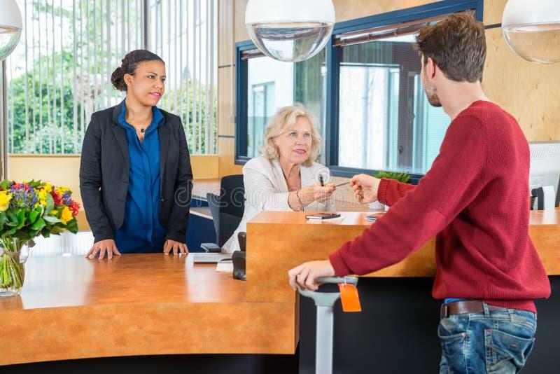 Επιχειρηματίες που συζητούν στο σύγχρονο λόμπι γραφείων στοκ εικόνα