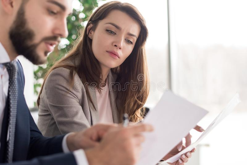 Επιχειρηματίες που συζητούν τα έγγραφα στην αρχή στοκ φωτογραφία