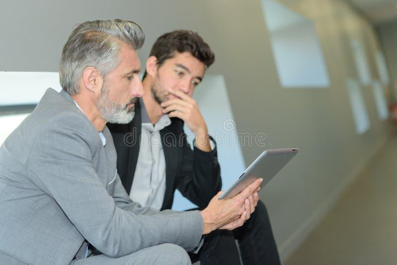 Επιχειρηματίες που συζητούν τα επιχειρησιακά ζητήματα στην αρχή στοκ φωτογραφία