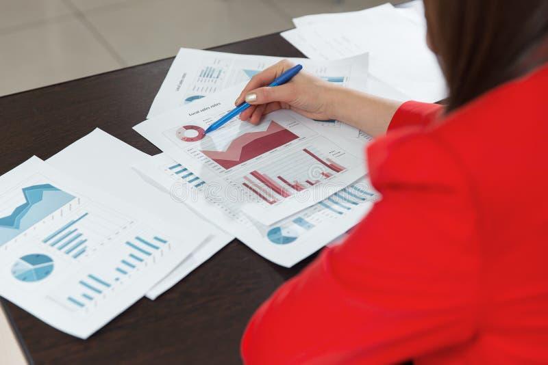 Επιχειρηματίες που συζητούν τα διαγράμματα και τις γραφικές παραστάσεις που παρουσιάζουν τα αποτελέσματα της επιτυχούς ομαδικής ε στοκ εικόνες