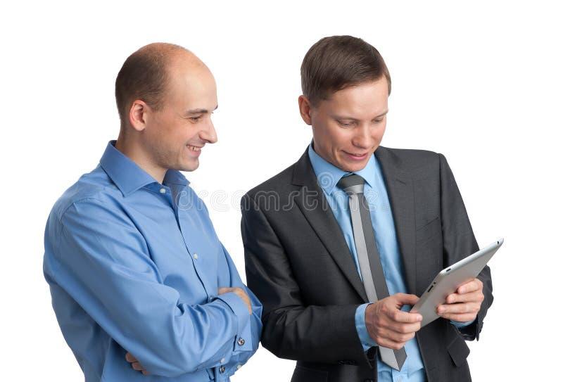 Επιχειρηματίες που συναντιούνται και που εξετάζουν τον υπολογιστή ταμπλετών στοκ εικόνα