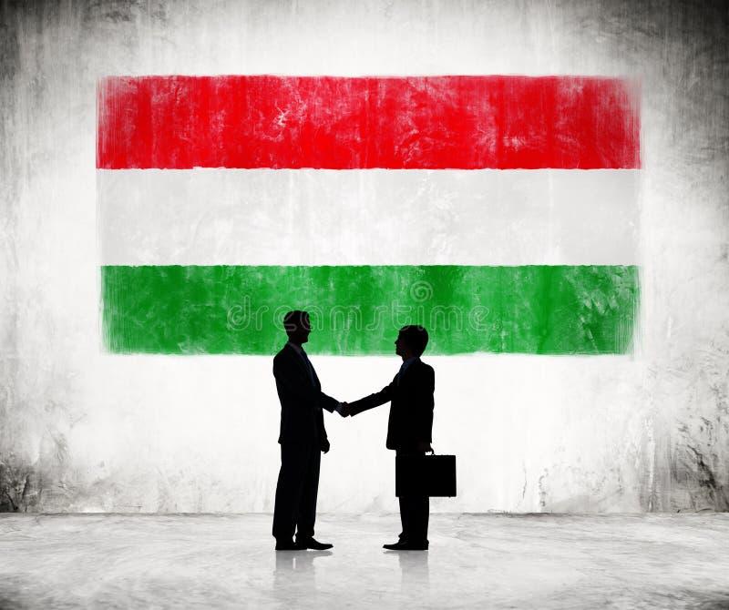 Επιχειρηματίες που τινάζουν τα χέρια με την ουγγρική σημαία στοκ φωτογραφία με δικαίωμα ελεύθερης χρήσης