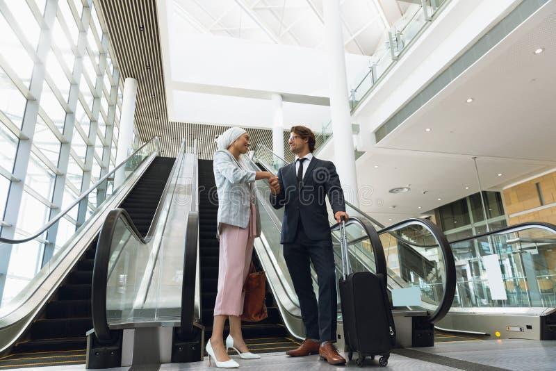 Επιχειρηματίες που τινάζουν τα χέρια ο ένας με τον άλλον κοντά στην κυλιόμενη σκάλα σε ένα σύγχρονο γραφείο στοκ εικόνες