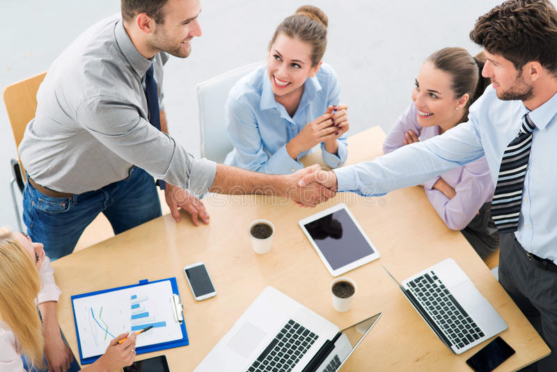 Επιχειρηματίες που τινάζουν τα χέρια πέρα από τον πίνακα στοκ εικόνα