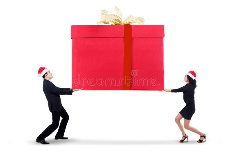 Επιχειρηματίες που φέρνουν ένα μεγάλο κιβώτιο δώρων στοκ εικόνα