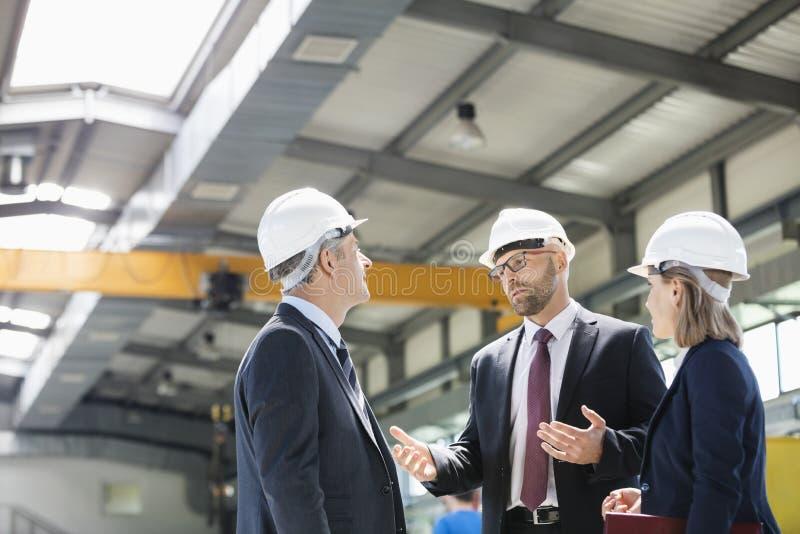 Επιχειρηματίες που φορούν hardhats που διοργανώνουν τη συζήτηση στη βιομηχανία μετάλλων στοκ φωτογραφία