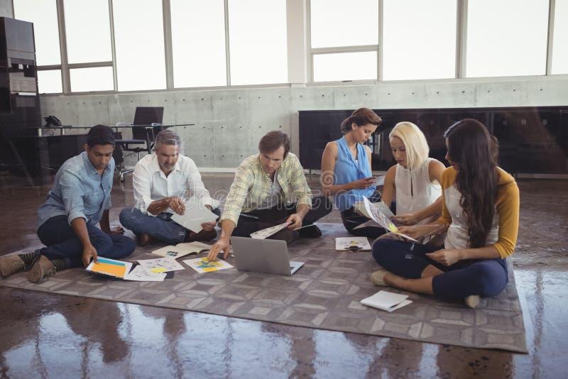 Επιχειρηματίες που χρησιμοποιούν τα διαγράμματα και το lap-top εργαζόμενος στην αρχή στοκ φωτογραφίες