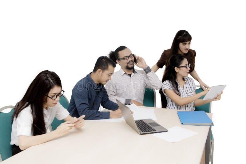 Επιχειρηματίες που χρησιμοποιούν τις ψηφιακές συσκευές στο στούντιο στοκ εικόνες με δικαίωμα ελεύθερης χρήσης
