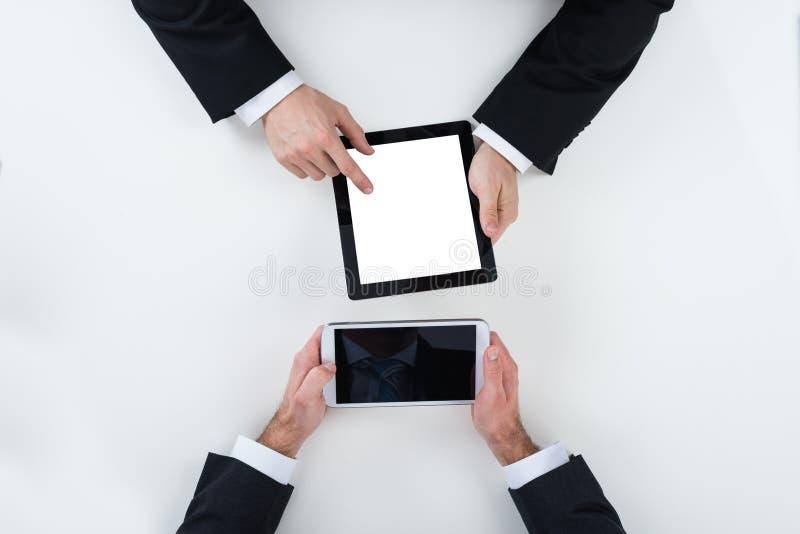 Επιχειρηματίες που χρησιμοποιούν τις ψηφιακές ταμπλέτες στον πίνακα στην αρχή στοκ εικόνα
