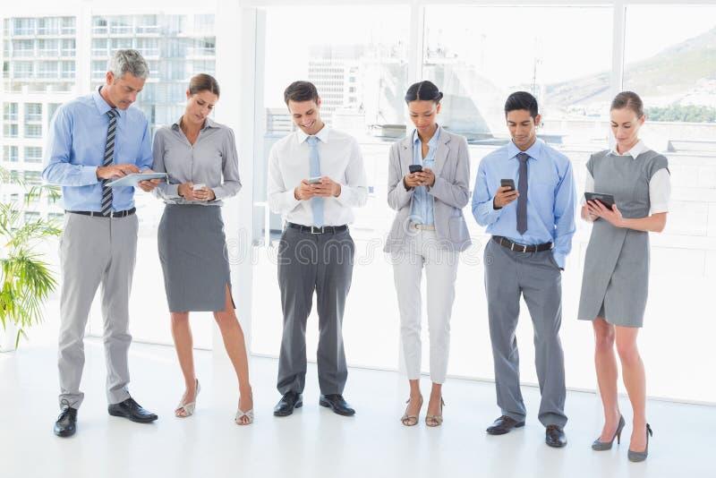 Επιχειρηματίες που χρησιμοποιούν το τηλέφωνό τους στοκ εικόνες