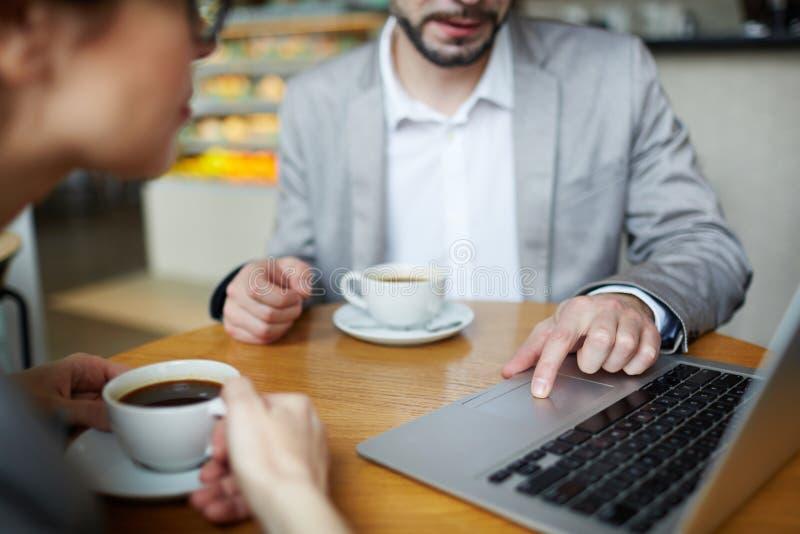 Επιχειρηματίες που χρησιμοποιούν το lap-top στη συνεδρίαση στον καφέ στοκ φωτογραφία