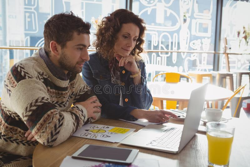 Επιχειρηματίες που χρησιμοποιούν το lap-top στον πίνακα στον καφέ στοκ φωτογραφίες με δικαίωμα ελεύθερης χρήσης