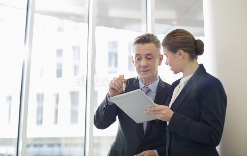 Επιχειρηματίες που χρησιμοποιούν το PC ταμπλετών στην αρχή στοκ φωτογραφία με δικαίωμα ελεύθερης χρήσης