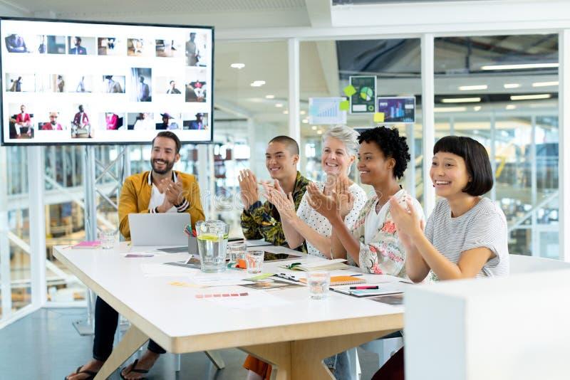 Επιχειρηματίες που χτυπούν τα χέρια καθμένος στη συνεδρίαση στη αίθουσα συνδιαλέξεων στοκ φωτογραφία με δικαίωμα ελεύθερης χρήσης