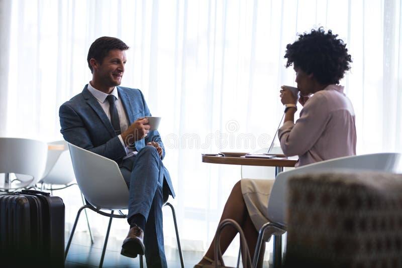 Επιχειρηματίες στο σαλόνι αναμονής αερολιμένων που έχει τον καφέ στοκ εικόνες