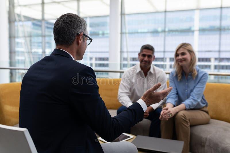 Επιχειρηματίες Caucaisans που αλληλεπιδρούν ο ένας με τον άλλον στον καναπέ στοκ εικόνες με δικαίωμα ελεύθερης χρήσης