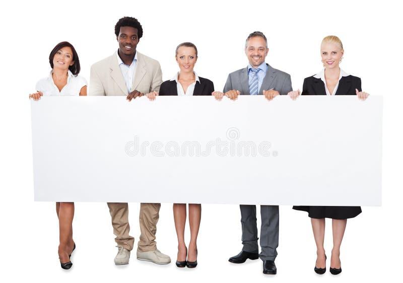 Επιχειρηματίες Multiethnic που κρατούν το μεγάλο πίνακα διαφημίσεων στοκ φωτογραφίες