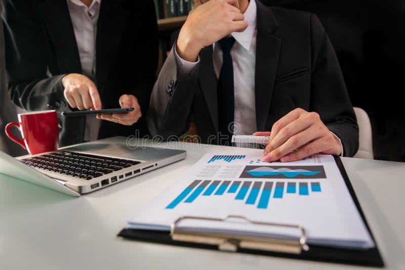 Επιχειρησιακά έγγραφα σχετικά με πίνακα γραφείων και δύο συναδέλφους που συζητούν τα στοιχεία στην αρχή στοκ εικόνα με δικαίωμα ελεύθερης χρήσης