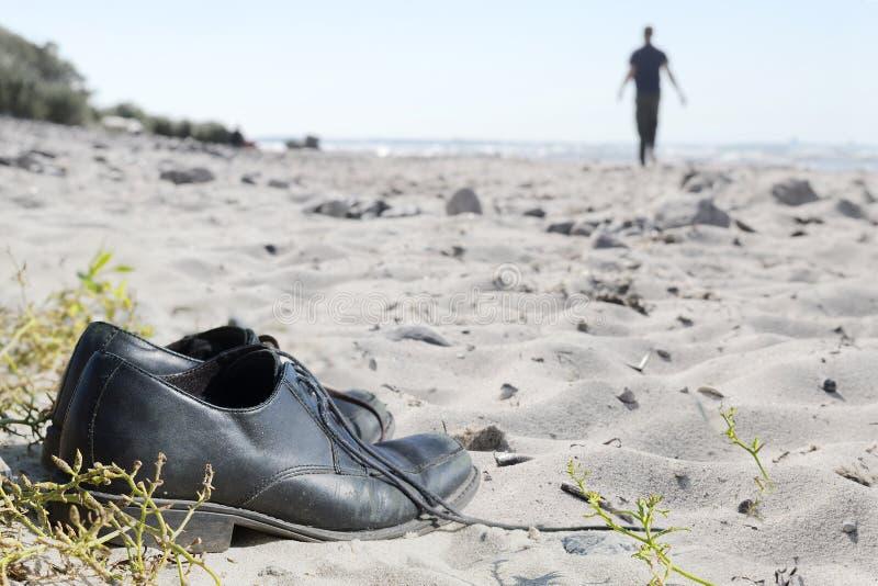 Επιχειρησιακά παπούτσια στην παραλία και ένα θολωμένο άτομο που περπατούν μακριά στο θόριο στοκ εικόνες με δικαίωμα ελεύθερης χρήσης