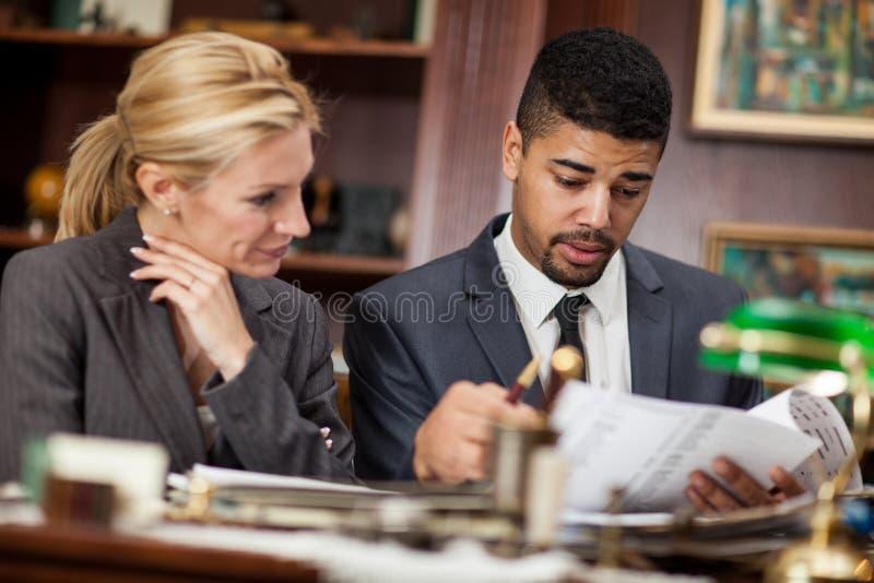 Επιχειρησιακές γυναίκες και ένας επιχειρηματίας στους φακέλλους αναθεώρησης γραφείων στοκ εικόνες