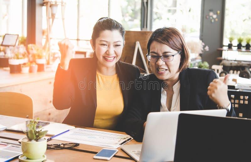 Επιχειρησιακές γυναίκες που γιορτάζουν τα καλά αποτελέσματα προγράμματος στοκ εικόνα