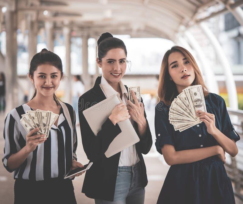 Επιχειρησιακές γυναίκες που καθιστούν τα μετρητά σε απευθείας σύνδεση στο lap-top στοκ εικόνες
