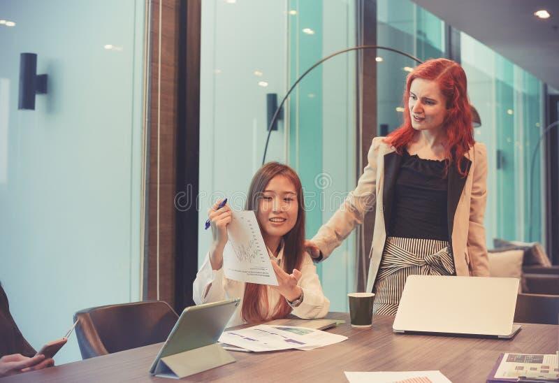 Επιχειρησιακές γυναίκες που μιλούν ο ένας στον άλλο στην αίθουσα συνεδριάσεων, πολυ ethn στοκ εικόνα