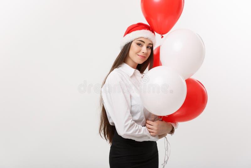 Επιχειρησιακή έννοια - η όμορφη νέα βέβαια επιχειρησιακή γυναίκα με το μπαλόνι εκμετάλλευσης καπέλων santa γιορτάζει για τα Χριστ στοκ εικόνα με δικαίωμα ελεύθερης χρήσης