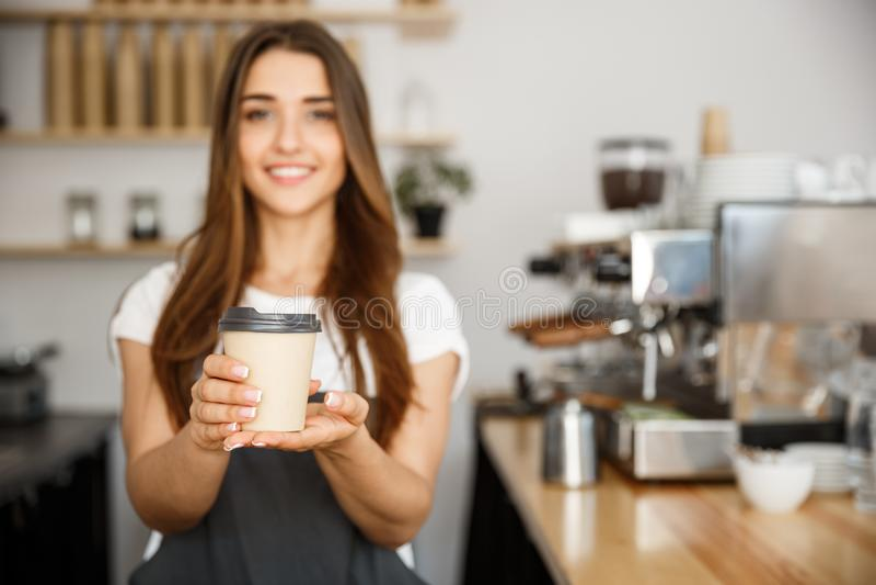 Επιχειρησιακή έννοια καφέ - η όμορφη καυκάσια κυρία που χαμογελά στη κάμερα προσφέρει το προϊόν μίας χρήσης παίρνει μαζί τον καυτ στοκ φωτογραφία