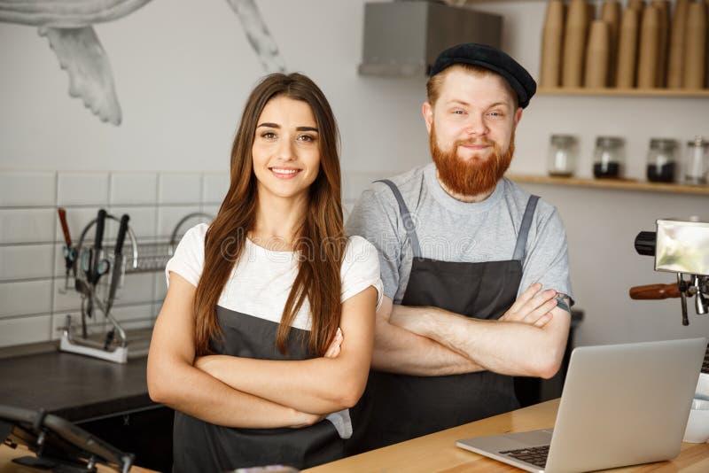 Επιχειρησιακή έννοια καφέ - το θετικό νέο γενειοφόρο άτομο και το όμορφο ελκυστικό γυναικείο barista συνδέουν στην ποδιά εξετάζον στοκ εικόνα