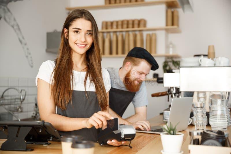 Επιχειρησιακή έννοια καφέ - όμορφο θηλυκό barista που δίνει την υπηρεσία πληρωμής για τον πελάτη με την πιστωτική κάρτα και το χα στοκ εικόνα