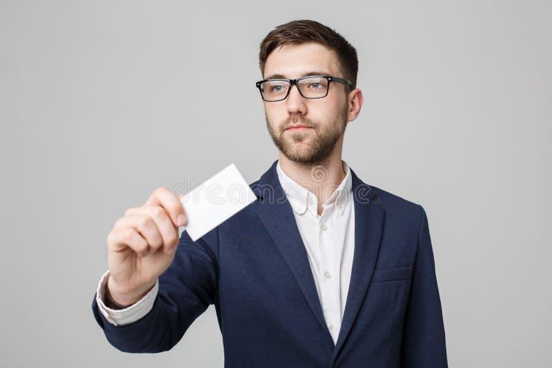 Επιχειρησιακή έννοια - όμορφο επιχειρησιακό άτομο πορτρέτου που παρουσιάζει κάρτα ονόματος με το βέβαιο πρόσωπο χαμόγελου Άσπρη α στοκ φωτογραφία με δικαίωμα ελεύθερης χρήσης