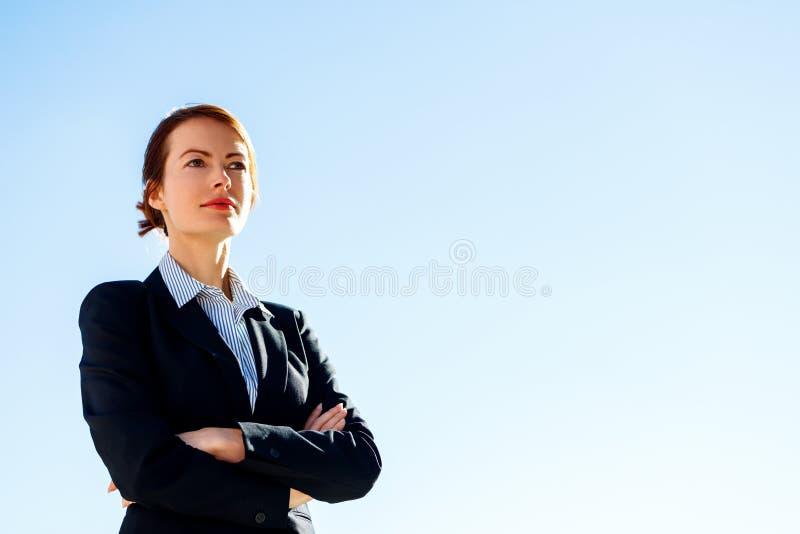 Επιχειρησιακή γυναίκα με τις διασχισμένες στάσεις χεριών ενάντια στο σαφή μπλε ουρανό στοκ εικόνα