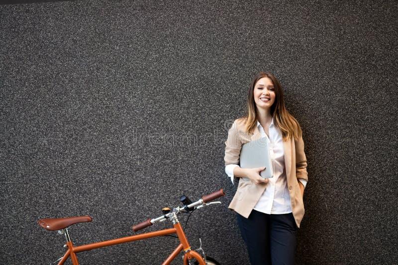 Επιχειρησιακή γυναίκα με το ποδήλατο για να εργαστεί στην αστική οδό στην πόλη Μεταφορά και υγιής έννοια τρόπου ζωής στοκ εικόνες