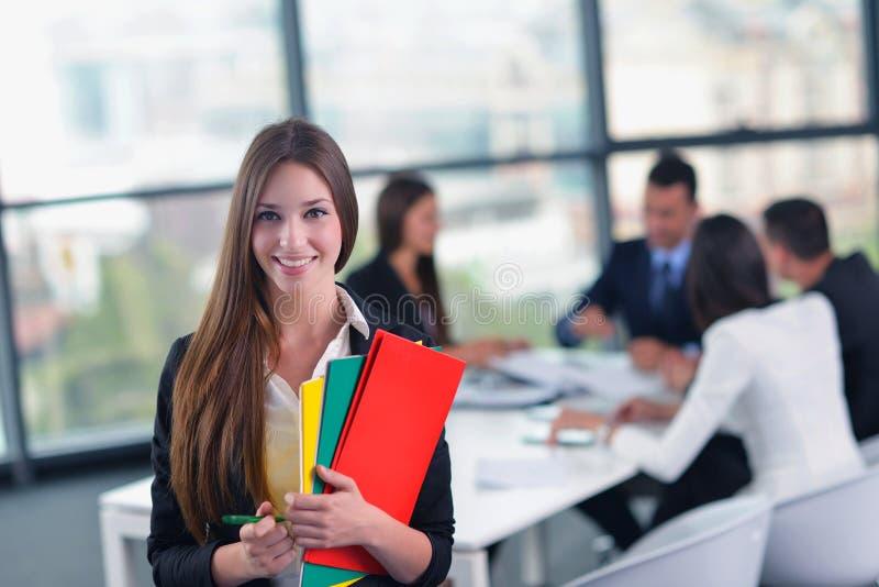 Επιχειρησιακή γυναίκα με το προσωπικό της στο υπόβαθρο στο γραφείο στοκ εικόνες