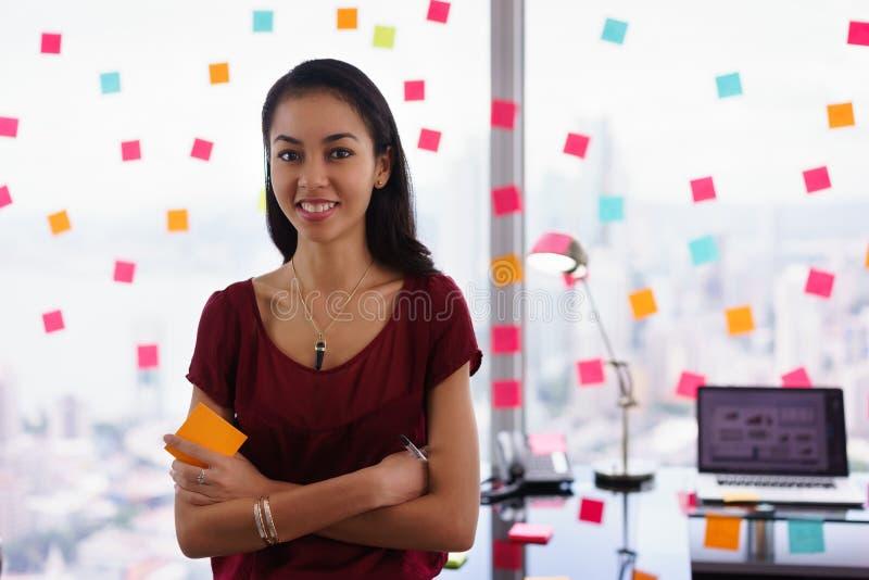 Επιχειρησιακή γυναίκα πορτρέτου που γράφει τις κολλώδεις σημειώσεις που χαμογελούν στη κάμερα στοκ εικόνες
