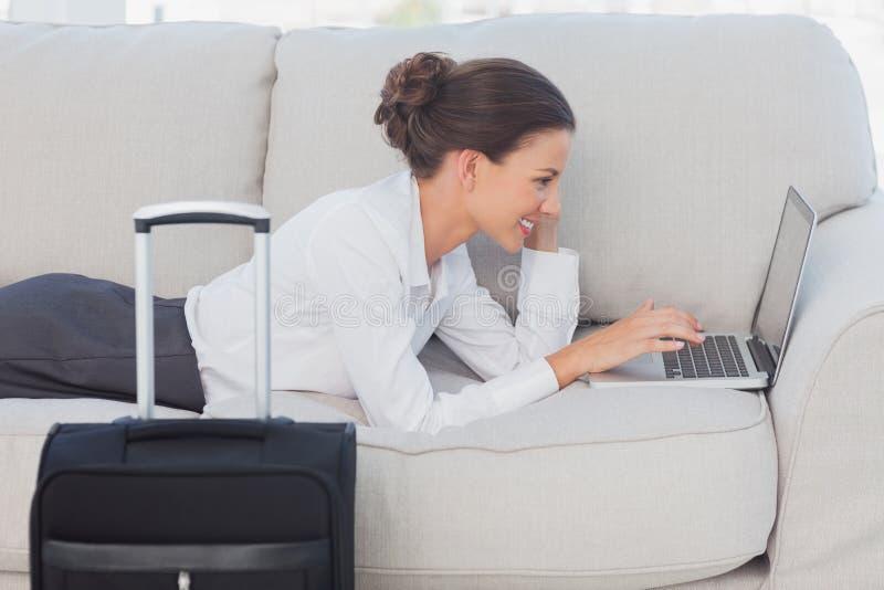 Επιχειρησιακή γυναίκα που βρίσκεται στον καναπέ με το lap-top και τη βαλίτσα στοκ φωτογραφία με δικαίωμα ελεύθερης χρήσης