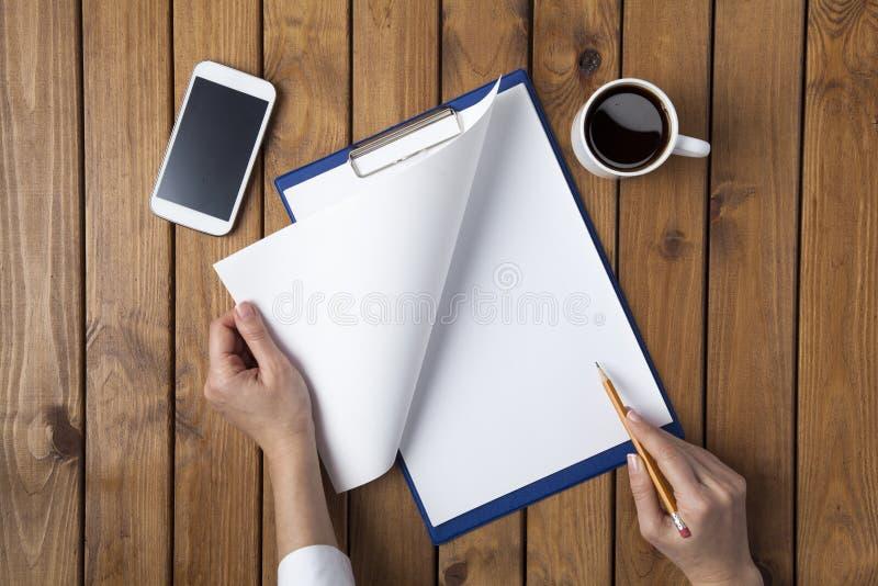Επιχειρησιακή γυναίκα που γράφει σε ένα κάτι ένα κενό έγγραφο στοκ φωτογραφία