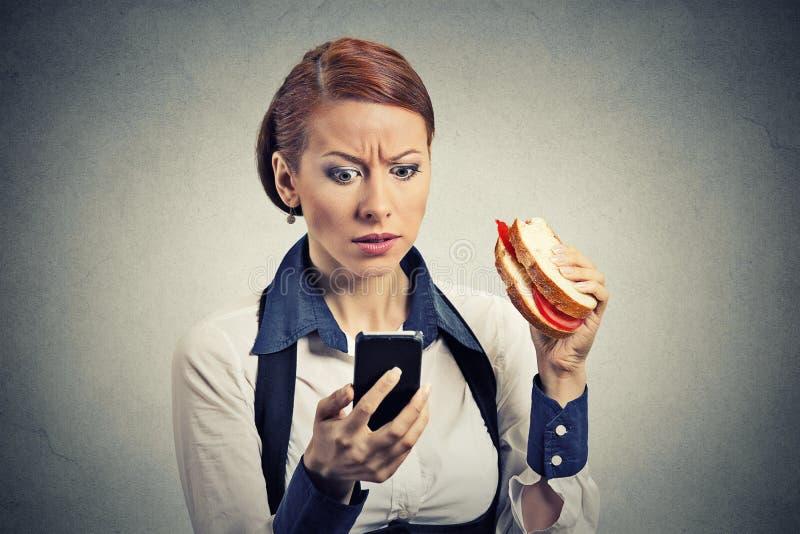 Επιχειρησιακή γυναίκα που εξετάζει το κινητό τηλέφωνό της που τρώει το σάντουιτς ψωμιού στοκ φωτογραφίες με δικαίωμα ελεύθερης χρήσης