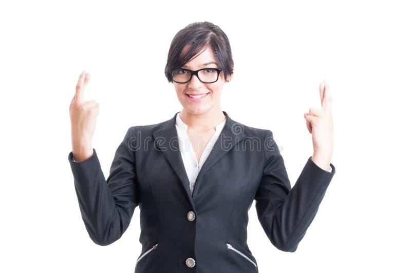 Επιχειρησιακή γυναίκα που επιθυμεί για την τύχη με τα διασχισμένα δάχτυλα στοκ εικόνα