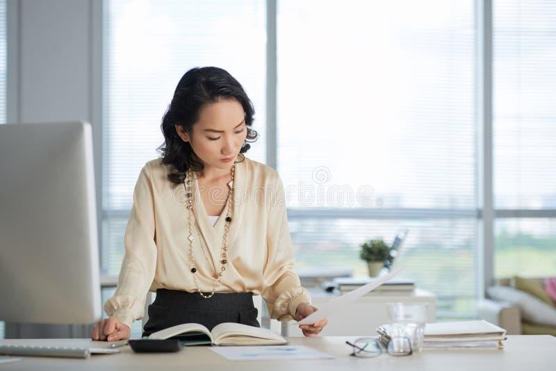 Επιχειρησιακή γυναίκα που εργάζεται με τα έγγραφα στοκ εικόνες