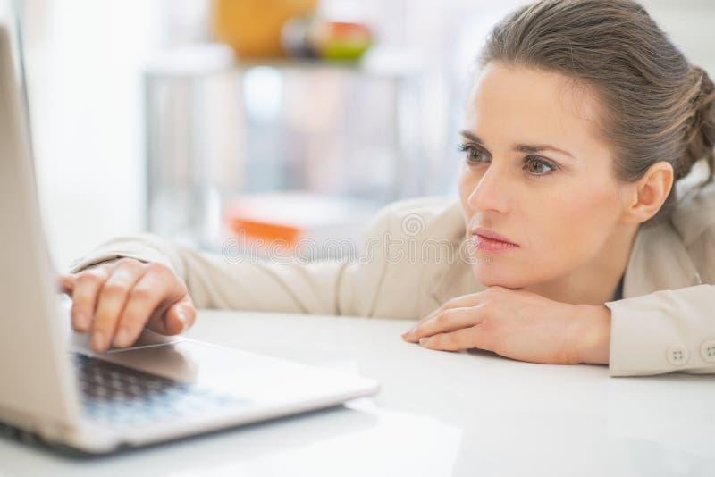 Επιχειρησιακή γυναίκα που εργάζεται με το lap-top στην αρχή στοκ εικόνες με δικαίωμα ελεύθερης χρήσης