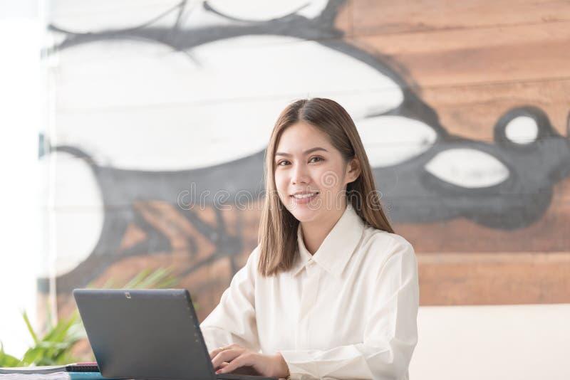 Επιχειρησιακή γυναίκα που εργάζεται στο χαμόγελο lap-top στοκ εικόνες